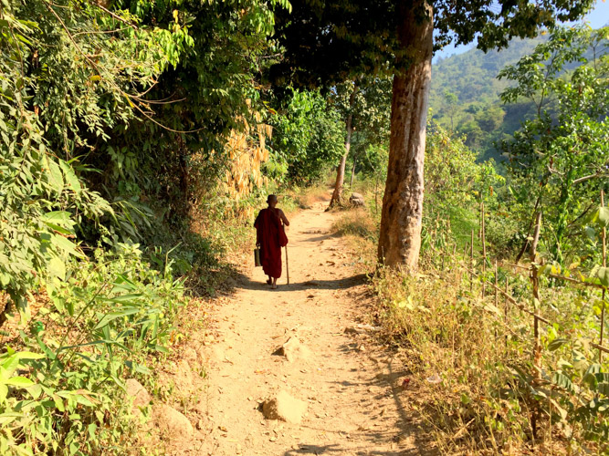 Local Buddhist pilgrim hiking in barefoot to the holy Golden Rock