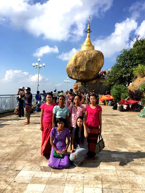 Familia birmana tomándose una foto de grupo con la Roca Dorada detrás, en el monte Kyaiktiyo