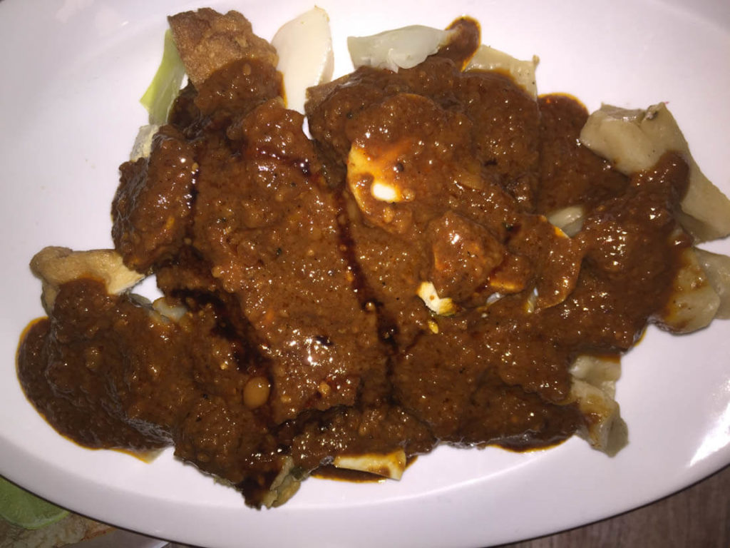 Siomay. fish dumplings with cabbage covered in peanut sauce