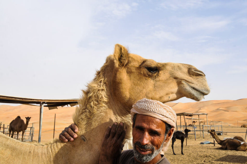 A Bedouin and his camel in Liwa Oasis