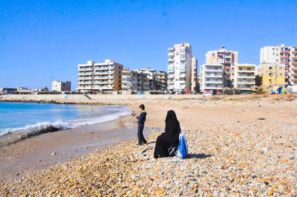 A woman and her son fishing at the beach of Tripoli, Lebanon